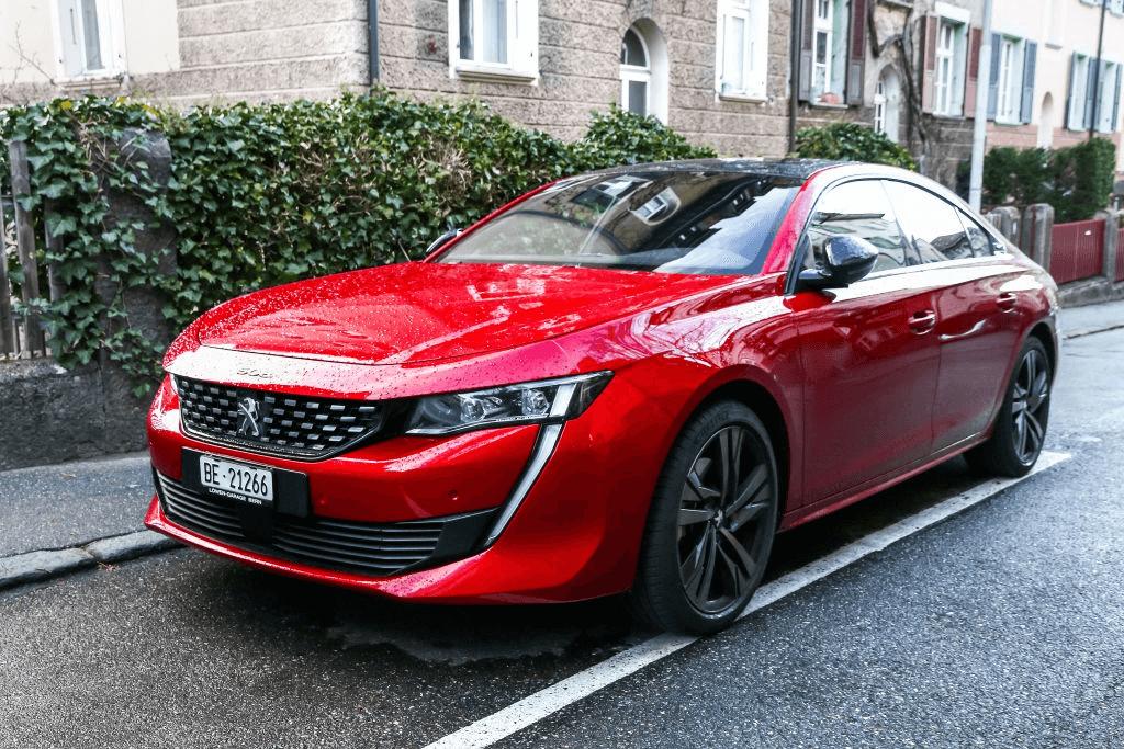 mobil sedan merah terparkir di jalanan